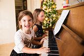 Joyful girls playing piano