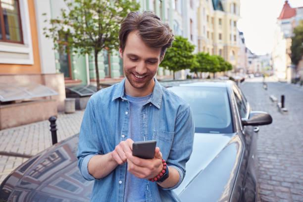 Joyful handsome male is chatting on smartphone stock photo