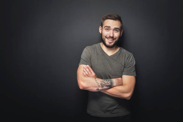 joyful, handsome man on a black background - tattoo stock photos and pictures