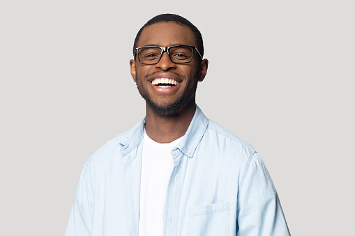 Joyful happy african american young man in eyeglasses portrait. Isolated on grey studio background smiling millennial black guy looking at camera, laughing, having fun, posing for photo head shot.