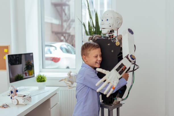 fröhlich fröhlicher junge umarmt einen roboter - lernfortschrittskontrolle stock-fotos und bilder