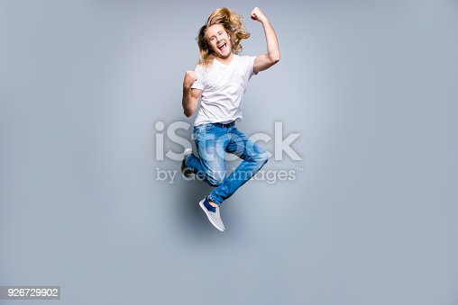 925466128 istock photo Joyful happy excited young man with blonde long hair is screaming and jumping up with raised fists, isolated on grey background 926729902
