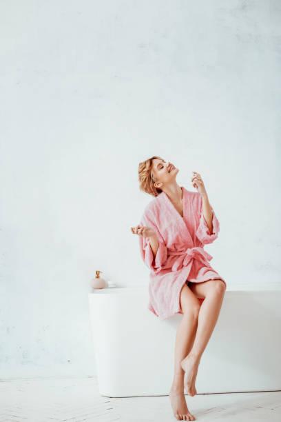 joyful happy woman sitting on the bath tube - accappatoio foto e immagini stock