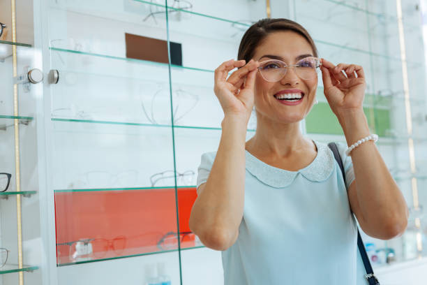 Joyful happy woman trying some eyeglasses on Stylish look. Joyful happy woman smiling while trying stylish eyeglasses on optical instrument stock pictures, royalty-free photos & images