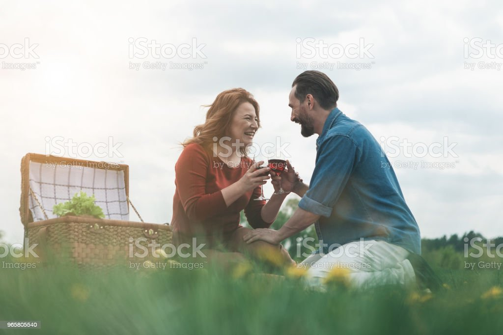 Joyful husband and wife drinking wine on meadow - Стоковые фото Алкоголь - напиток роялти-фри