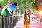 Cheerful young Indian teenage girl standing in the nature with colorful umbrella during summer sunny day outdoors.