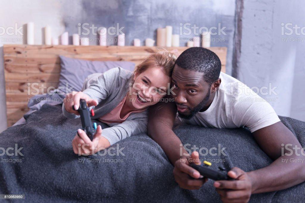 Joyful international couple playing video games at home stock photo