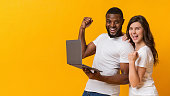 istock Joyful interracial couple holding laptop, celebrating success and exclaiming in excitement 1201187147