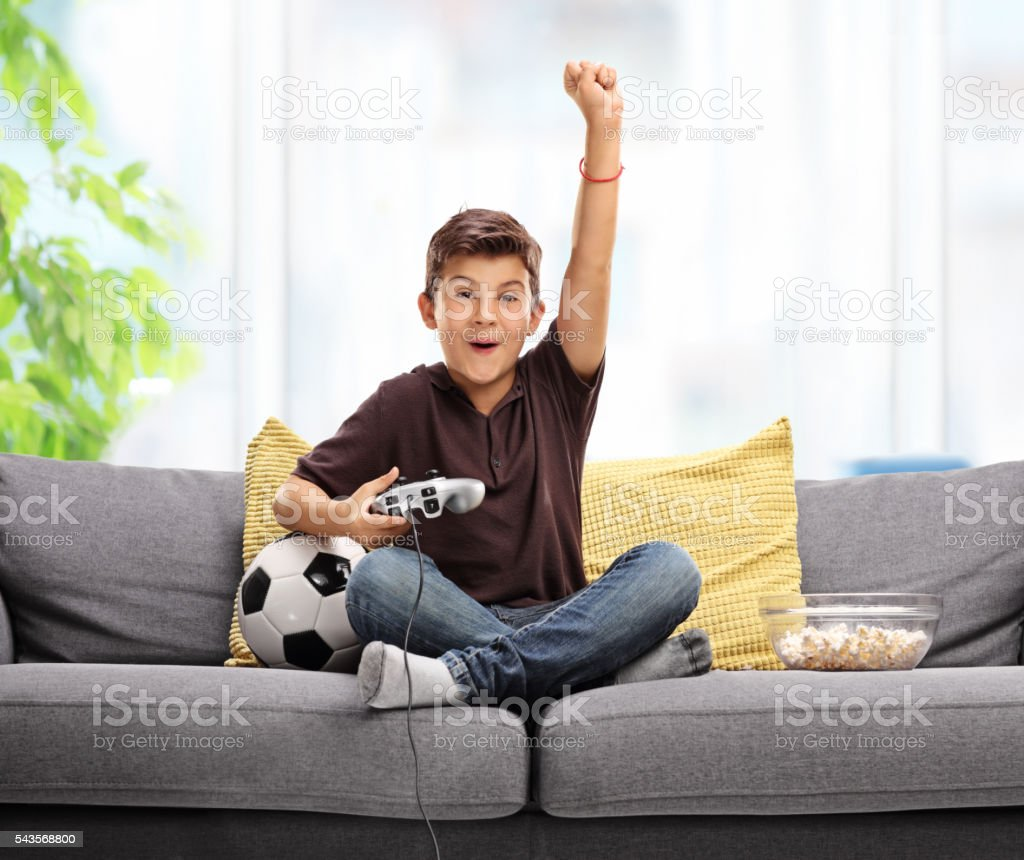 Joyful kid playing football video game stock photo