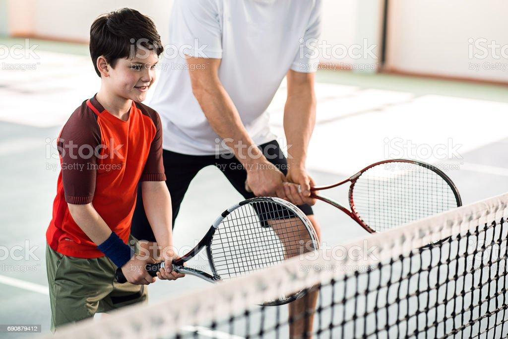 Joyful kid playing tennis with father stock photo