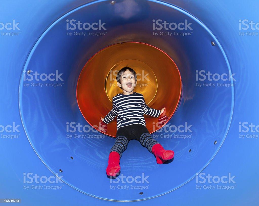 Joyful kid sliding in tube slide stock photo