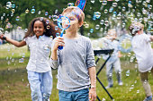Multi-ethnic group of little kids having fun at green public park while making colorful soap bubbles, adorable fair-haired boy standing on foreground