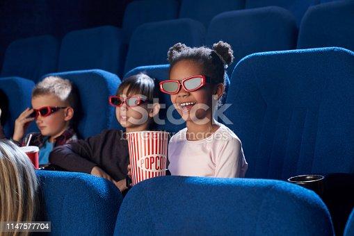 istock Joyful kids watching movie in 3D glasses, in cinema. 1147577704