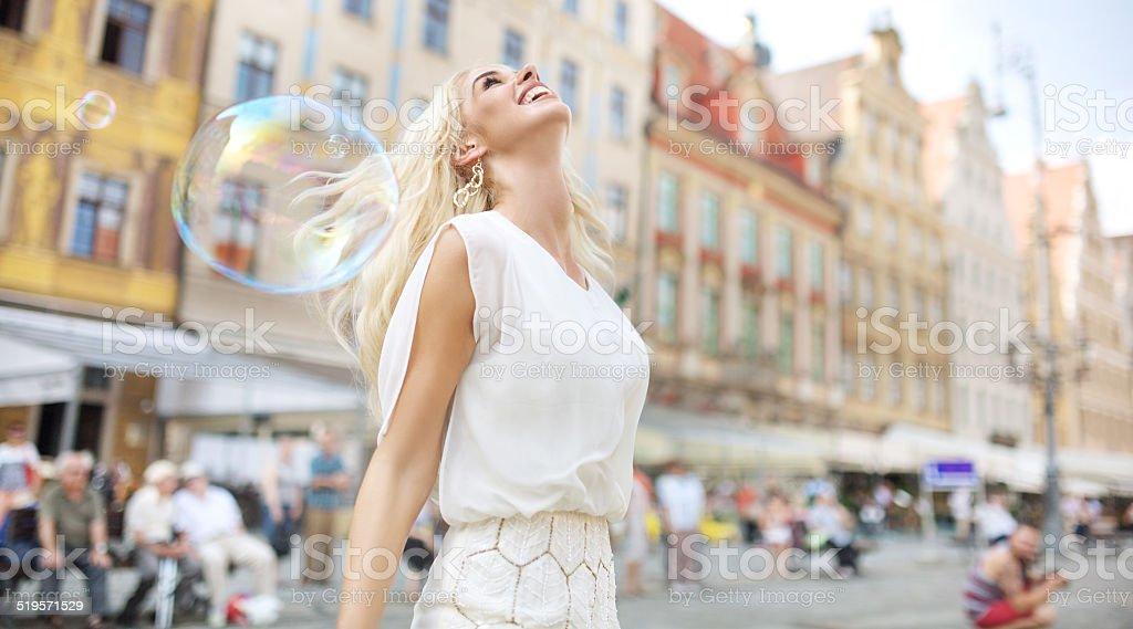 Joyful lady among the soap bubbles stock photo