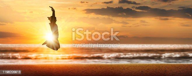 istock joyful leap at the sunset beach 1198205613