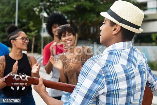 istock Joyful listening young people at a concert of street muscian 825207882