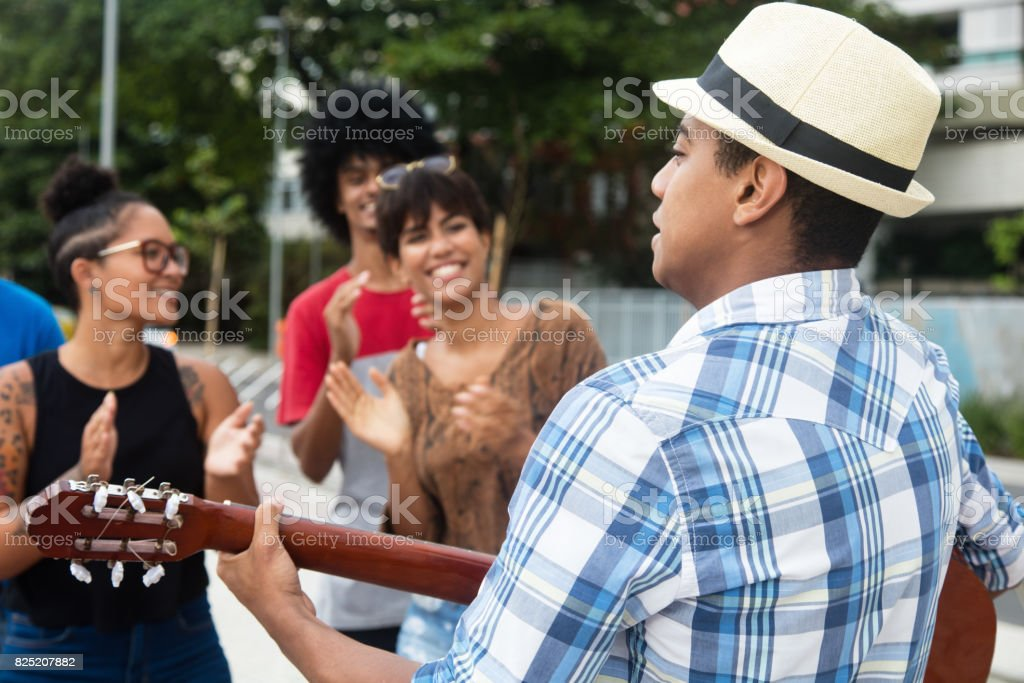Joyful listening young people at a concert of street muscian stock photo