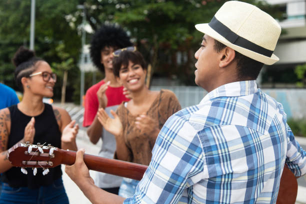 Joyful listening young people at a concert of street muscian Joyful listening young people at a concert of street muscian outdoor in the city in the summer folk music stock pictures, royalty-free photos & images