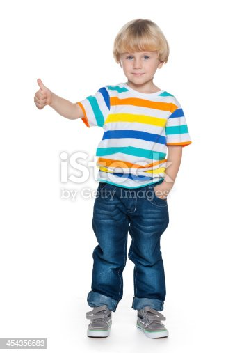 A joyful fashion little boy holds his thumb up on the white background