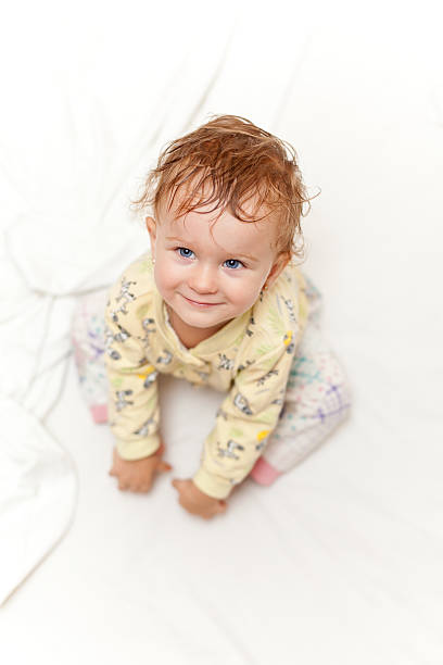 Joyful little girl sitting on bed stock photo