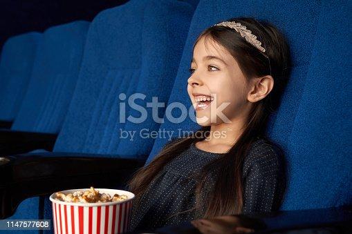 istock Joyful little girl watching movie, laughing in cinema. 1147577608