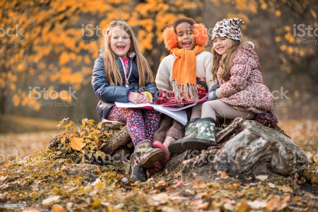 Joyful little girls with notebooks in the park. stock photo