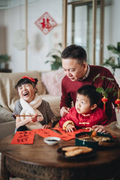 joyful little granddaughter and grandson practising chinese calligraphy for chinese new year on couplets with grandfather - chinese new year stock pictures, royalty-free photos & images