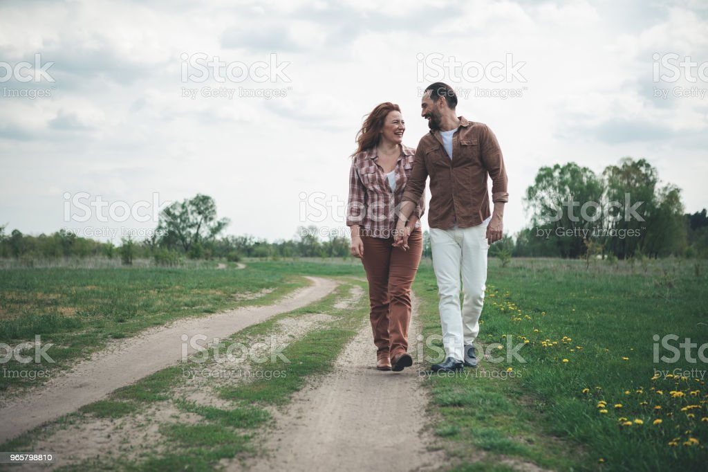 Joyful lovers walking on meadow path - Royalty-free Adult Stock Photo