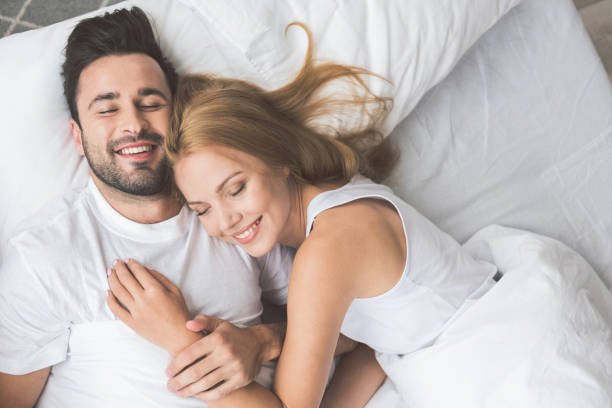 joyful loving couple luxuriating in bedroom together - łóżko zdjęcia i obrazy z banku zdjęć