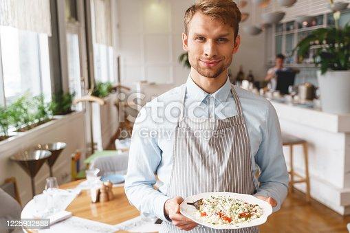istock Joyful male waiter holding plate of fresh salad 1225932888