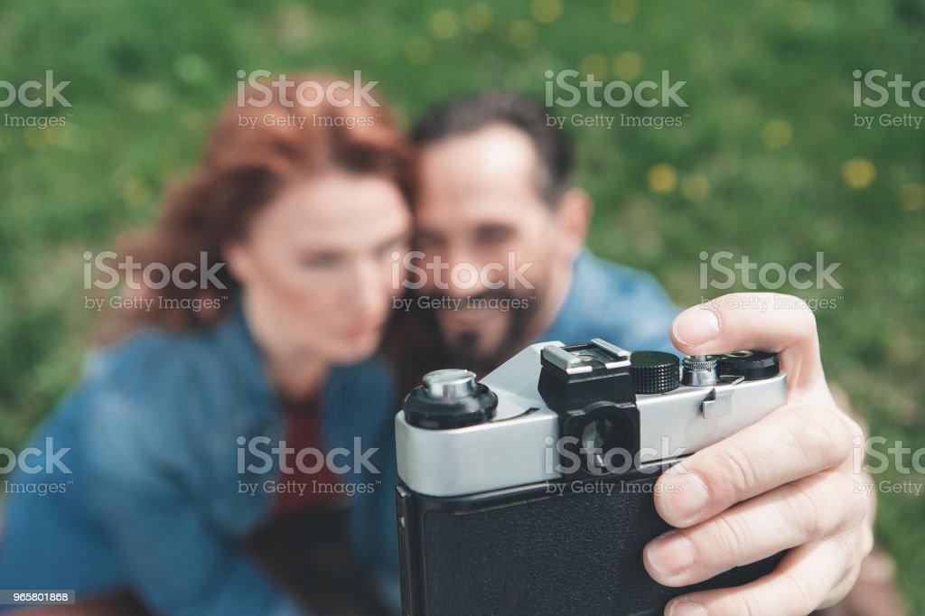 Vrolijke man en vrouw nemen van foto's op grasland - Royalty-free Activiteit - Bewegen Stockfoto