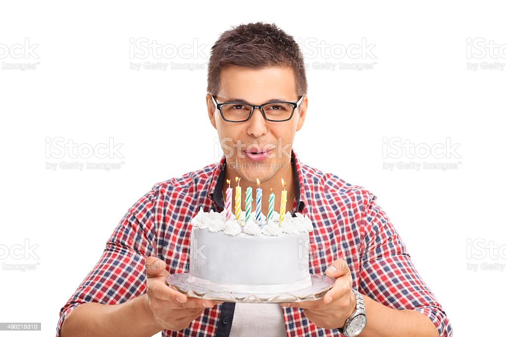 Joyful man blowing candles on a birthday cake stock photo