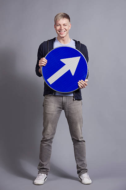 Joyful man holding round blue sign with arrow. stock photo