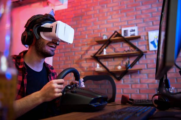 fröhliche mann ist elektronische unterhaltung zu hause genießen. - steuerungstechnik stock-fotos und bilder