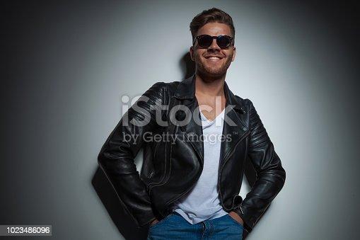 542972720 istock photo joyful man wearing a black leather jacket and sunglasses 1023486096