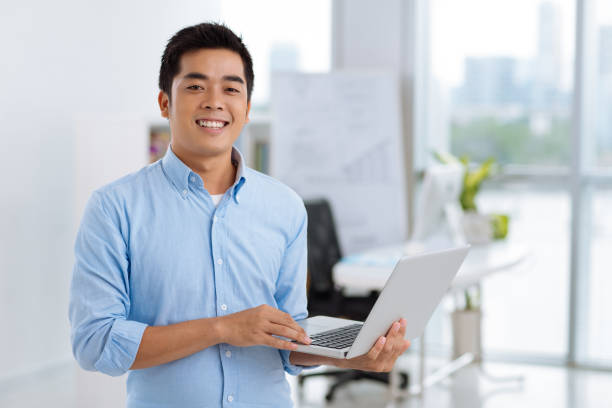 Joyful Manager Posing for Photography Waist-up portrait of joyful Asian manager looking at camera with toothy smile while holding laptop in hands, interior of modern office on background vietnamese ethnicity stock pictures, royalty-free photos & images