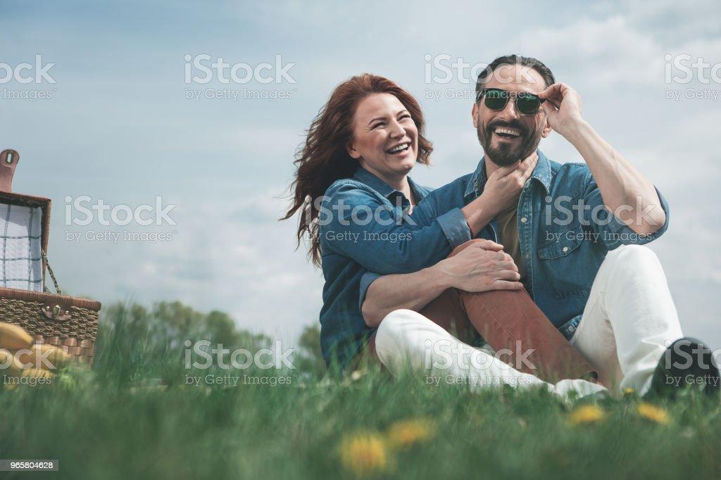 Joyful married couple having picnic on grassland - Стоковые фото Близость роялти-фри