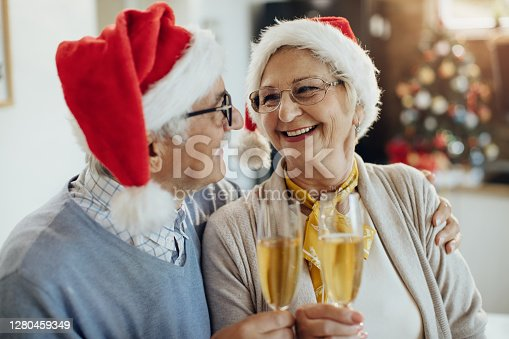 Happy senior woman and her husband toasting with Champagne while celebrating Christmas at home.