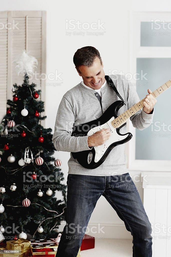 Joyful mature man playing guitar during Christmas royalty-free stock photo