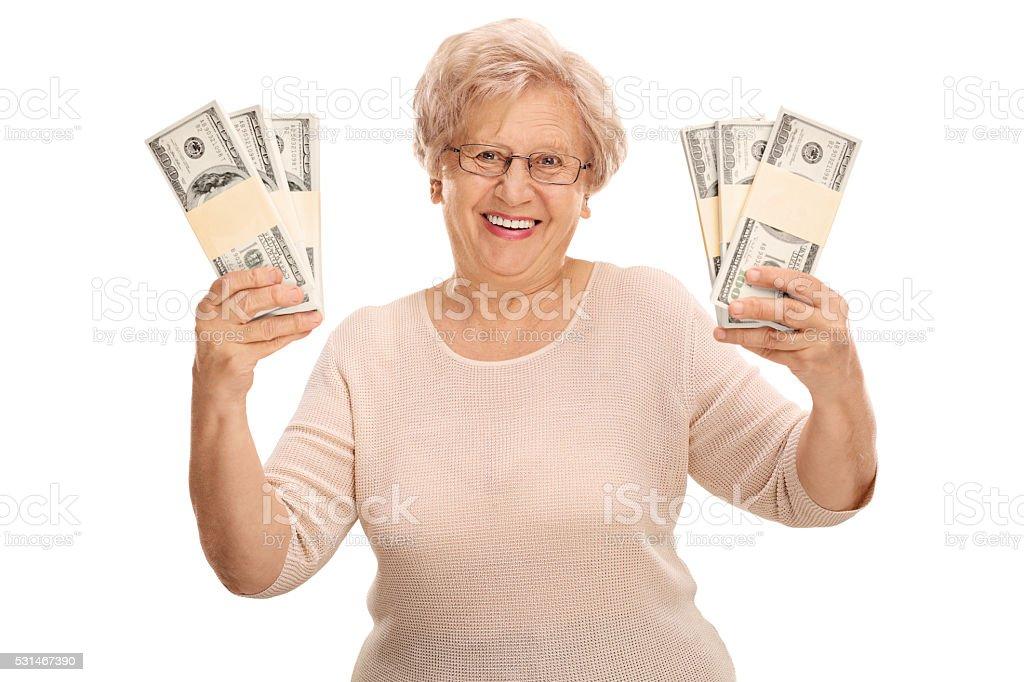 Joyful mature woman holding money stock photo