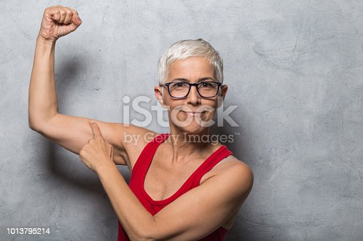 Woman showing her muscles and pointing finger at it
