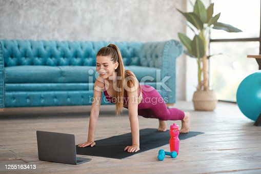 Happy millennial girl doing plank exercise to online class on laptop computer at home