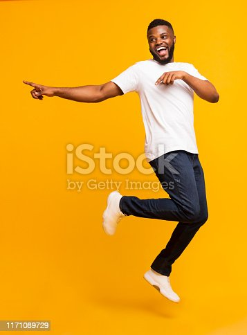 istock Joyful millennial guy jumping on air and pointing aside 1171089729