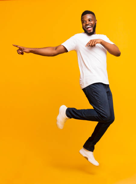 Joyful millennial guy jumping on air and pointing aside Joyful black millennial guy jumping on air and pointing aside, free space mid air stock pictures, royalty-free photos & images