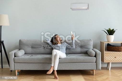 istock Joyful mixed race woman turning on cooler system air conditioner. 1182206292
