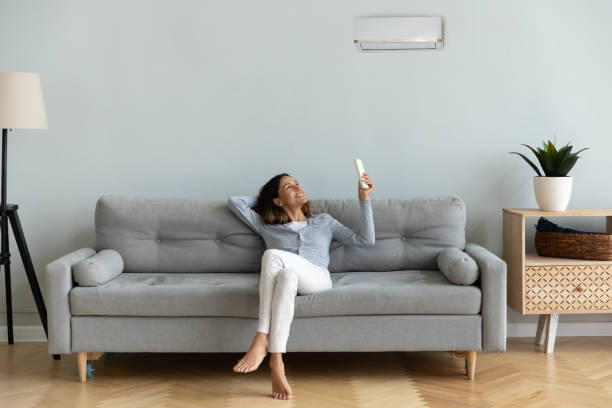 Joyful mixed race woman turning on cooler system air conditioner. Front view full length joyful young mixed race woman relaxing on cozy couch in living room, holding remote controller, turning on cooler system air conditioner, setting comfortable temperature. comfortable stock pictures, royalty-free photos & images