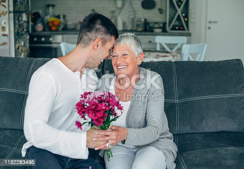 Young man giving flowers bouquet to his mother