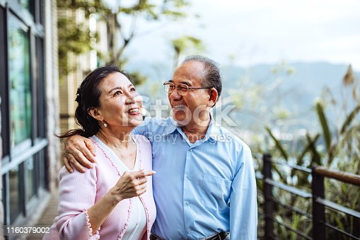 Smiling senior Taiwanese couple hugging in backyard