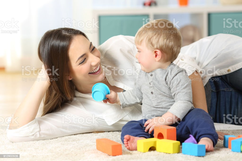 Joyful mother and baby playing on a carpet stock photo