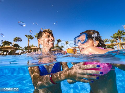 Joyful Mother And Daughter Having Fun In Pool During Vacations In Egypt